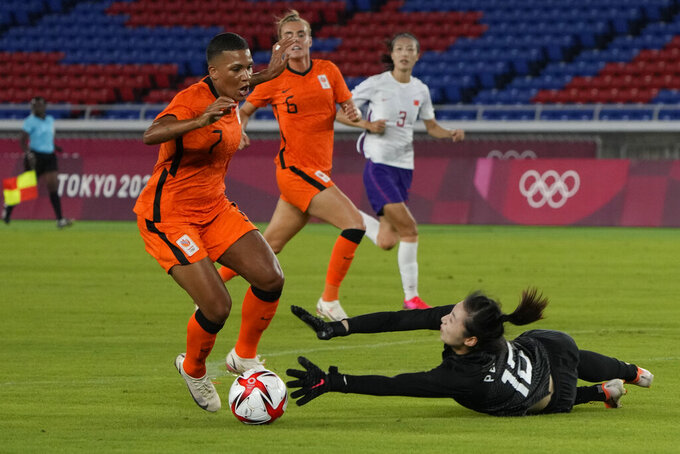 Netherlands' Shanice van de Sanden, left, dribbles the ball to score her side's opening goal as China's Peng Shimeng tries to stop during a women's soccer match at the 2020 Summer Olympics, Tuesday, July 27, 2021, in Yokohama, Japan. (AP Photo/Kiichiro Sato)