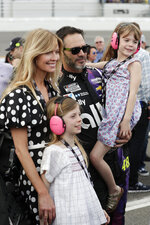 Jimmie Johnson, center, gathers next to his car with his wife Chandra Janway, left, and children Genevieve, front left, and Lydia, right, before the NASCAR Daytona 500 auto race at Daytona International Speedway, Sunday, Feb. 16, 2020, in Daytona Beach, Fla. (AP Photo/John Raoux)