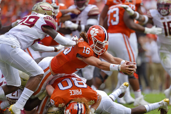 FILE - In this Oct. 12, 2019, file photo, Clemson quarterback Trevor Lawrence (16) stretches out for a touchdown while defended by Florida State's Isaiah Bolden (29) during the first half of an NCAA college football game in Clemson, S.C. Lawrence was selected to The Associated Press preseason All-America first-team, Tuesday, Aug. 25, 2020. (AP Photo/Richard Shiro, File)
