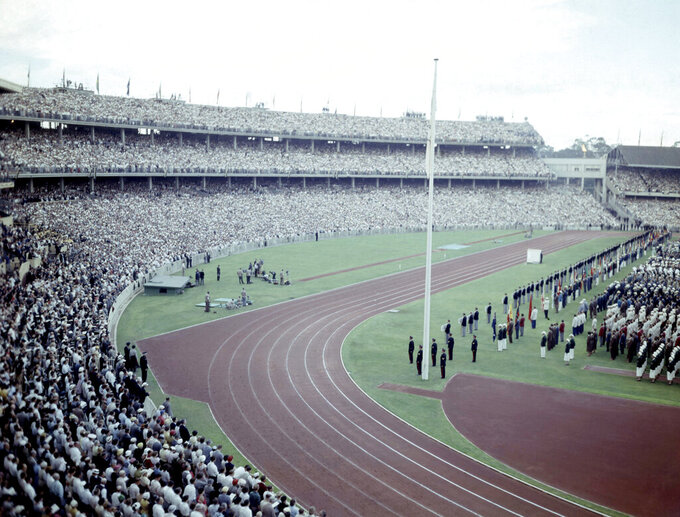 FILE - In this Nov. 22, 1956, file photo, a general view shows crowds and athletes in the Olympic Stadium, in Melbourne, Australia, during the opening ceremony of XVI Olympic Games. An Australian push to host the 2032 Olympics was elevated overnight to the status of preferred bid, and the people of Brisbane and southeast Queensland state woke up to the news Thursday, Feb. 25, 2021 (AP Photo, File)