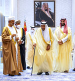 In this photo released by Saudi Royal Palace, Saudi King Salman, center, and Crown Prince Mohammed bin Salman, right, welcome Oman's Sultan Haitham bin Tariq, left, at Neom Royal Palace, in the Tabuk Province of northwestern Saudi Arabia, Sunday, July 11, 2021. Sultan Haitham started the first visit by an Omani ruler in years against the backdrop of renewed diplomatic efforts to end the war in Yemen and the sultanate's worsening economic woes. A framed photo shows Saudi Arabia's founder, the late King Abdul Aziz Al Saud. (Bandar Aljaloud/Saudi Royal Palace via AP)