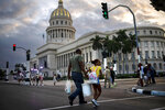 In this Nov 8, 2019 photo, people walk next to the Capital building, with its dome recently restored by Russian specialists in Havana, Cuba. The city will celebrate its 500th anniversary on Nov. 16. (AP Photo/Ramon Espinosa)