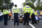Demonstrators sit on the road blocking traffic during an Extinction Rebellion climate change protest in London, Tuesday, Sept 1, 2020. (AP Photo/Alberto Pezzali)