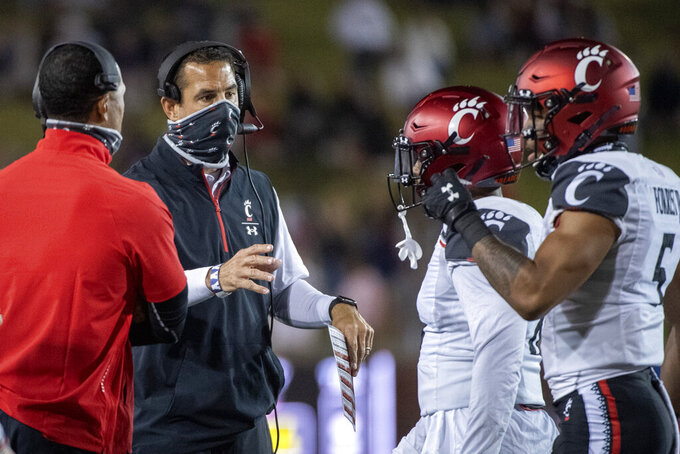 Cincinnati head coach Luke Fickell, second from left, confers with linebacker Jarrell White, second from right, and safety Derrick Forest, right, during the first half of an NCAA college football game against SMU, Saturday, Oct. 24, 2020, in Dallas. (AP Photo/Jeffrey McWhorter)