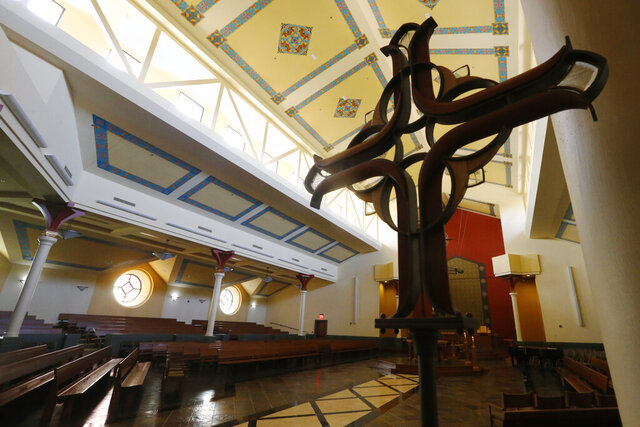An empty sanctuary awaits parishioners on Palm Sunday at Saint Mary's Catholic Church Sunday April 5, 2020, in Richmond, Va. The church is not holding Mass but is opening the sanctuary for prayer. (AP Photo/Steve Helber)