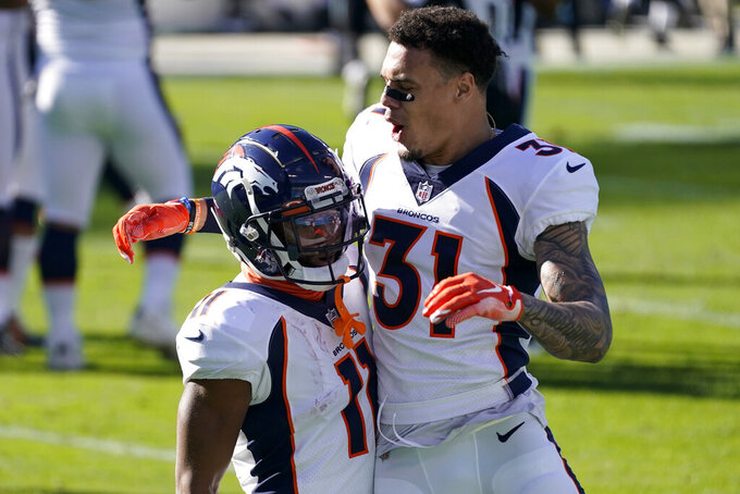 Denver Broncos wide receiver Diontae Spencer, left, celebrates after scoring with safety Justin Simmons during the first half of an NFL football game against the Carolina Panthers Sunday, Dec. 13, 2020, in Charlotte, N.C. (AP Photo/Gerry Broome)