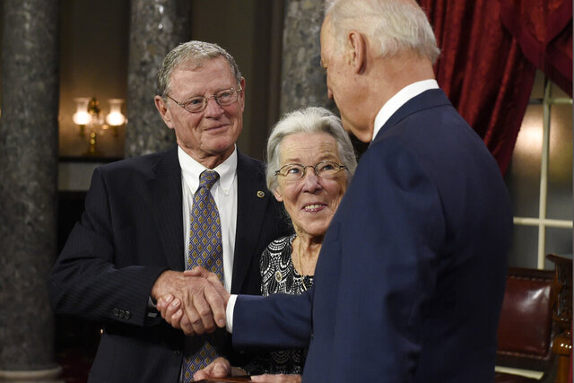 FILE - In this Jan. 6, 2015 file photo, Vice President Joe Biden shakes hands with Sen. James Inhofe, R-Okla., accompanied by Inhofe's wife Kay, center, after taking the Senate oath during a ceremonial re-enactment swearing-in ceremonyin Washington. Inhofe's wife, Kay, suffered what he described as a mild stroke last week, causing him to miss the first day of impeachment trial proceedings, Oklahoma's senior U.S. senator said on Tuesday, Jan, 21, 2020. (AP Photo/Susan Walsh File)