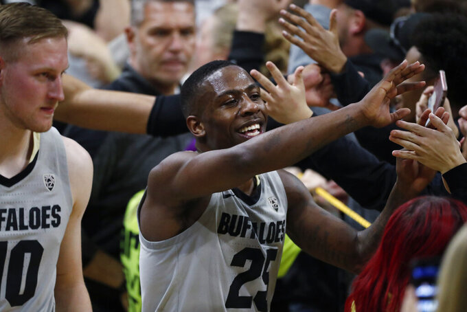 Colorado guard McKinley Wright IV is congratulated by fans as they storm the court after the second half of an NCAA college basketball game against Oregon Thursday, Jan. 2, 2020, in Boulder, Colo. Colorado won 74-65. (AP Photo/David Zalubowski)