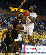 Michigan guard Zavier Simpson (3) makes a layup as Appalachian State guard Adrian Delph (20) defends during the second half of an NCAA college basketball game, Tuesday, Nov. 5, 2019, in Ann Arbor, Mich. (AP Photo/Carlos Osorio)