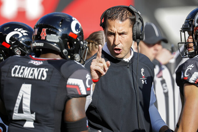 FILE - In this Saturday, Nov. 3, 2018, file photo, Cincinnati head coach Luke Fickell, right, speaks with linebacker Malik Clements (4) before an NCAA college football game against Navy in Cincinnati. Nobody saw Cincinnati coming in the American Athletic Conference last year. Not even Luke Fickell, who guided the team to a seven-victory improvement in his second season as Bearcats coach. Best to expect the unexpected in the AAC. The league has been fertile ground for fast turnarounds since it rose from the ashes of the old Big East in 2013. (AP Photo/John Minchillo, File)