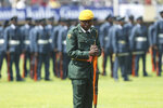 A soldier stands guard as the remains of the late former Zimbabwean leader, Robert Mugabe arrive at the National Sports stadium during a funeral procession in Harare, Saturday, Sept, 14, 2019. African heads of state and envoys are gathering to attend a state funeral for Mugabe, whose burial has been delayed for at least a month until a special mausoleum can be built for his remains. (AP Photo/Tsvangirayi Mukwazhi)