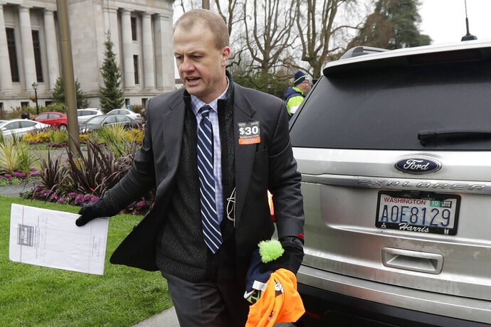 FILE - In this Jan. 13, 2020, file photo, initiative activist Tim Eyman, who is also running as an independent for Washington governor, carries a clipboard as he walks next to his expired car registration tabs before attending a rally on the first day of the 2020 session of the Washington legislature, at the Capitol in Olympia, Wash. Washington Attorney General Bob Ferguson is challenging the lavish personal spending of bankrupt anti-tax activist and candidate for governor Eyman. Ferguson says Eyman's assets must be preserved so he can pay his debts to the state. The Seattle Times reports that Eyman's bankruptcy filings show he's been spending nearly $24,000 a month over the past year. (AP Photo/Ted S. Warren, File)