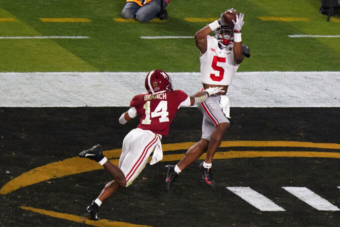 Ohio State wide receiver Garrett Wilson catches a touchdown pass in front of Alabama defensive back Brian Branch during the second half of an NCAA College Football Playoff national championship game, Monday, Jan. 11, 2021, in Miami Gardens, Fla. (AP Photo/Wilfredo Lee)