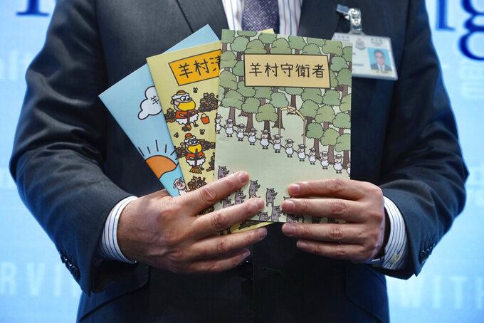 Li Kwai-wah, senior superintendent of Police National Security Department, poses with evidence including three children's books on stories that revolve around a village of sheep which has to deal with wolves from a different village, before a press conference in Hong Kong Thursday, July 22, 2021. Hong Kong's national security police on Thursday arrested five people from a trade union of the General Association of Hong Kong Speech Therapists on suspicion of conspiring to publish and distribute seditious material, in the latest arrests made amid a crackdown on dissent in the city.(AP Photo/Vincent Yu)