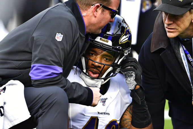 Baltimore Ravens linebacker Chris Board, center, is helped after being injured during the first half of an NFL football game against the Buffalo Bills in Orchard Park, N.Y., Sunday, Dec. 8, 2019. (AP Photo/Adrian Kraus)