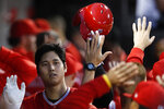 Los Angeles Angels' Shohei Ohtani celebrates with teammates after hitting a three-run home run against the Chicago White Sox during the third inning of a baseball game Saturday, Sept. 7, 2019, in Chicago. (AP Photo/Jim Young)