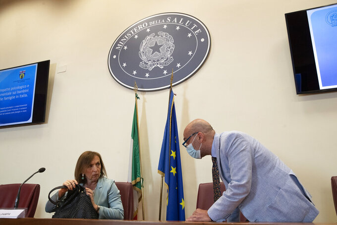 Sandra Zampa,  Health Ministry Undersecretary, left, and psychiatrist Fabrizio Starace, arrive for a press conference at the Italian Health Ministry to present the results of an investigation on the psychological and behavioral impact the coronavirus lockdown has had on children and adolescents in Italy, in Rome, Tuesday, June 16, 2020. (AP Photo/Alessandra Tarantino)