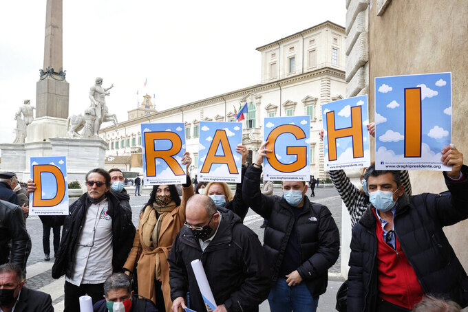 """A group of supporters hold placards reading """"Draghi President"""" in front of the Quirinale Presidential palace in Rome Wednesday, Feb. 3, 2021. Former European Central Bank President Mario Draghi arrived for talks with Italian President Sergio Mattarella to discuss a mandate to form a new government. (Mauro Scrobogna/LaPresse via AP)"""