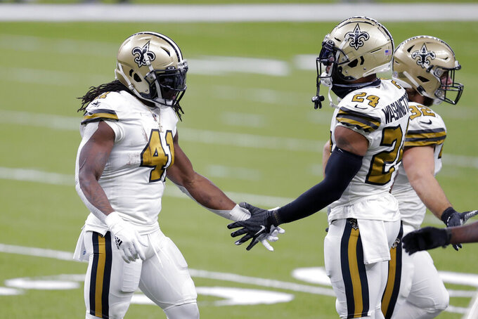 New Orleans Saints running back Alvin Kamara (41) is greeted by running back Dwayne Washington (24) after his second touchdown carry in the first half of an NFL football game against the Minnesota Vikings in New Orleans, Friday, Dec. 25, 2020. (AP Photo/Brett Duke)
