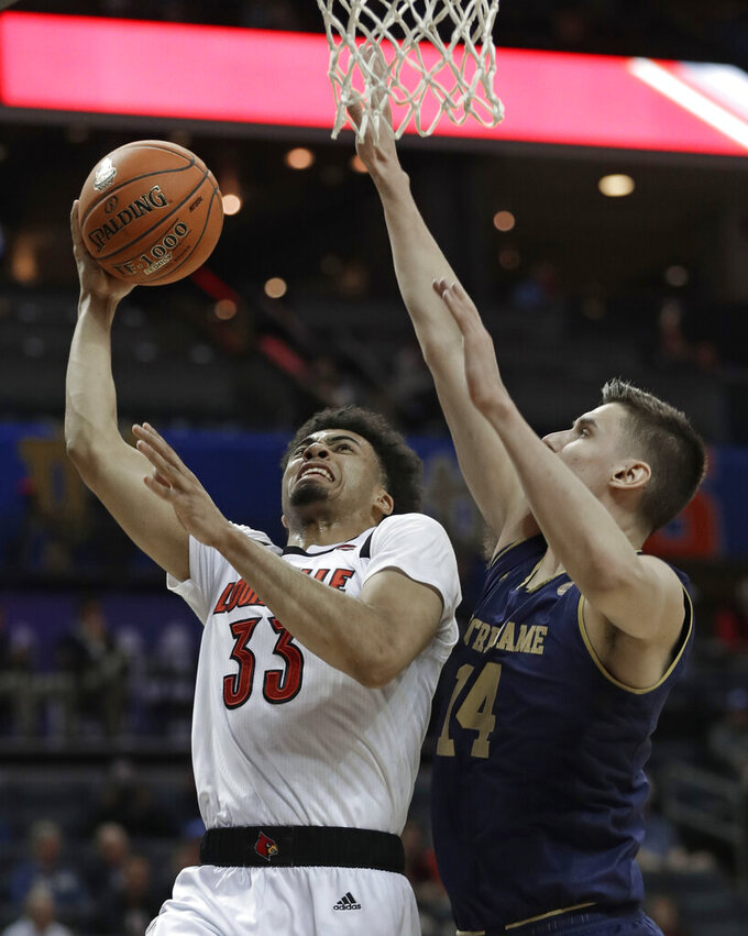 Louisville's Jordan Nwora (33) shoots against Notre Dame's Nate Laszewski (14) during the first half of an NCAA college basketball game in the Atlantic Coast Conference tournament in Charlotte, N.C., Wednesday, March 13, 2019. (AP Photo/Nell Redmond)