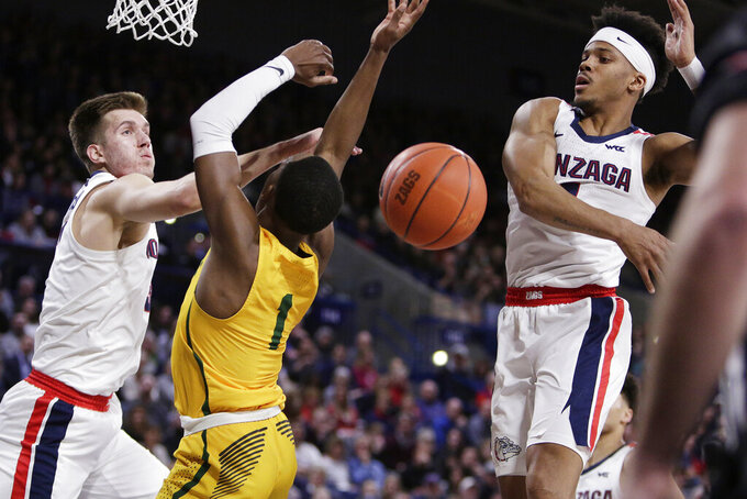 San Francisco guard Jamaree Bouyea, center, has his shot blocked by Gonzaga guard Admon Gilder, right, while also pressured by forward Filip Petrusev during the first half of an NCAA college basketball game in Spokane, Wash., Thursday, Feb. 20, 2020. (AP Photo/Young Kwak)