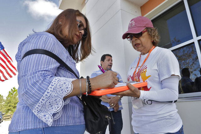 In this Dec. 10, 2019 photo, Hispanic Federation Canvasser Ana M. Vigo, right, registers Maria Moralez, left, to vote as Ivan Baez Munoz looks on outside the Polk Coutny Tax Collectors office in Davenport, Fla. (AP Photo/Chris O'Meara)