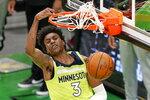 Minnesota Timberwolves forward Jaden McDaniels (3) dunks against the Boston Celtics in the first quarter of an NBA basketball game, Friday, April 9, 2021, in Boston. (AP Photo/Elise Amendola)