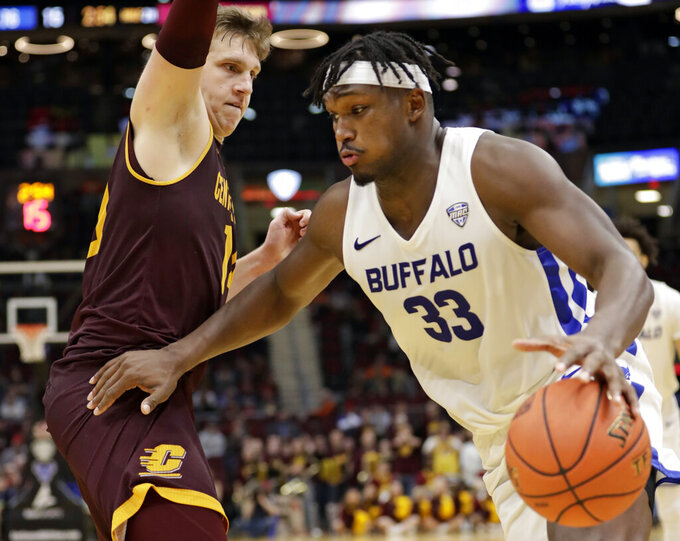 Buffalo's Nick Perkins (33) drives past Central Michigan's David DiLeo (14) during the second half of an NCAA college basketball game in the semifinals of the Mid-American Conference men's tournament Friday, March 15, 2019, in Cleveland. (AP Photo/Tony Dejak)