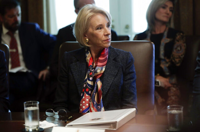 FILE - In this Oct. 21, 2019, file photo, Education Secretary Betsy DeVos listening to President Donald Trump during a Cabinet meeting in the Cabinet Room of the White House in Washington. DeVos is calling on Congress to consider splitting her department's financial aid operation into a separate federal agency with the flexibility to operate like a private bank. (AP Photo/Pablo Martinez Monsivais, File)
