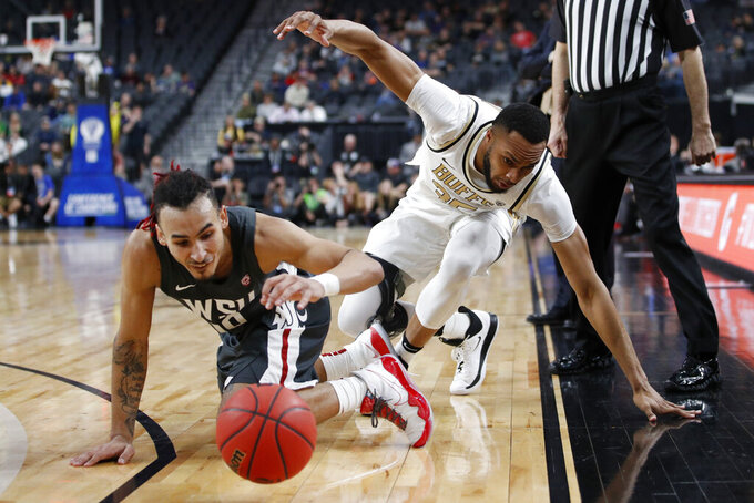 Washington State's Isaac Bonton, left, and Colorado's Dallas Walton scramble for the ball during the first half of an NCAA college basketball game in the first round of the Pac-12 men's tournament Wednesday, March 11, 2020, in Las Vegas. (AP Photo/John Locher)