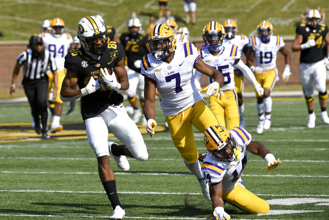Missouri wide receiver Tauskie Dove, left, catches an 86-yard pass for a touchdown as LSU safety safety JaCoby Stevens (7) and Maurice Hampton Jr. (14) defend during the first half of an NCAA college football game Saturday, Oct. 10, 2020, in Columbia, Mo. (AP Photo/L.G. Patterson)