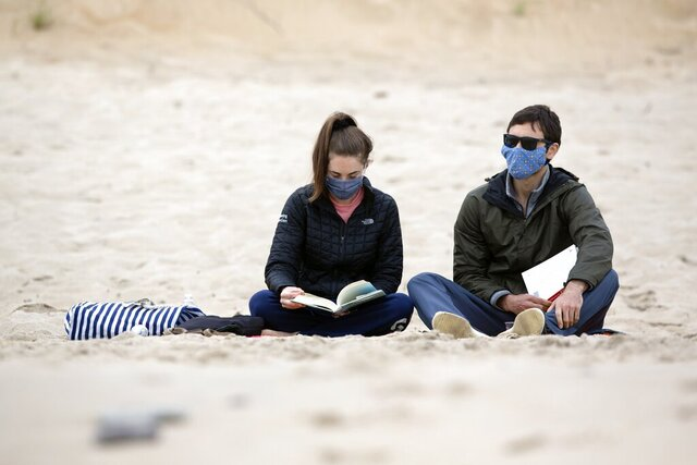 Amanda Pensack, left, and Derek Engelking, of Weymouth, Mass., sit on Marconi Beach, part of Cape Cod National Seashore, Monday, May 25, 2020, in Wellfleet, Mass. (AP Photo/Michael Dwyer)
