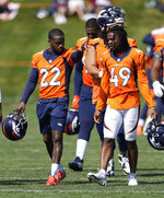 Denver Broncos strong safety Kareem Jackson, left, chats with cornerback Mac McCain III after NFL football practice at the team's headquarters, Thursday, Aug. 19, 2021, in Englewood, Colo. (AP Photo/David Zalubowski)