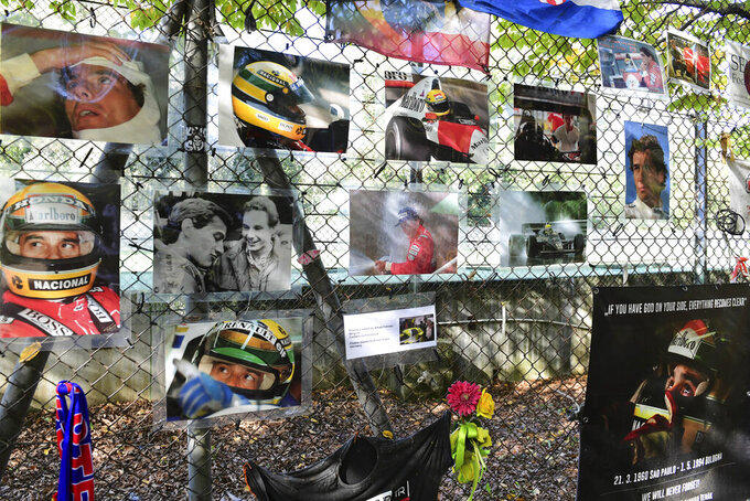 Pictures of late Brazilian race car driver Ayrton Senna hangs on the the corner where he was died, during the third practice session ahead of Sunday's Emilia Romagna Formula One Grand Prix, at the Enzo and Dino Ferrari racetrack, in Imola, Italy, Saturday, Oct. 31, 2020. (Jennifer Lorenzini, Pool via AP)