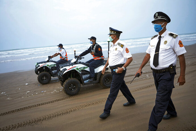 Moroccan police officers wearing face masks patrol Ain Diab beach in Casablanca, Morocco, Wednesday, Sept.23, 2020. Morocco first decreed lockdown measures on March 20. Today, police checks are part of the scenery in hard-hit Casablanca, the country's economic powerhouse, or Marrakech, a major tourist destination at a standstill. (AP Photo/Abdeljalil Bounhar)