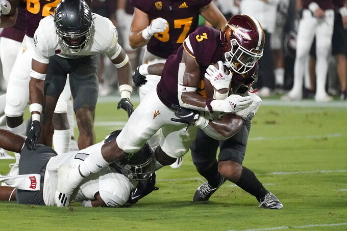 Arizona State running back Rachaad White (3) is hit by UNLV defensive back Bryce Jackson, right, during the first half of an NCAA college football game, Saturday, Sept. 11, 2021, in Tempe, Ariz. (AP Photo/Matt York)
