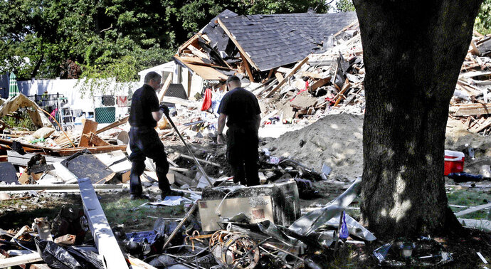 FILE - In this Sep. 21, 2018, file photo, fire investigators pause while searching the debris at a home which exploded last week following a gas line failure in Lawrence, Mass. The series of natural gas explosions and fires in Massachusetts last September has cost provider Columbia Gas of Massachusetts more than $1 billion. (AP Photo/Charles Krupa, File)