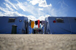 Afghan refugees stand in an Italian Red Cross refugee camp, in Avezzano, Italy, Tuesday, Aug. 31, 2021. This quarantine camp in Abruzzo, central Italy, where 1,250 migrants are hosted, is expected to close in a week as the quarantine expires and they are moved to other structures to apply for asylum. (AP Photo/Andrew Medichini)