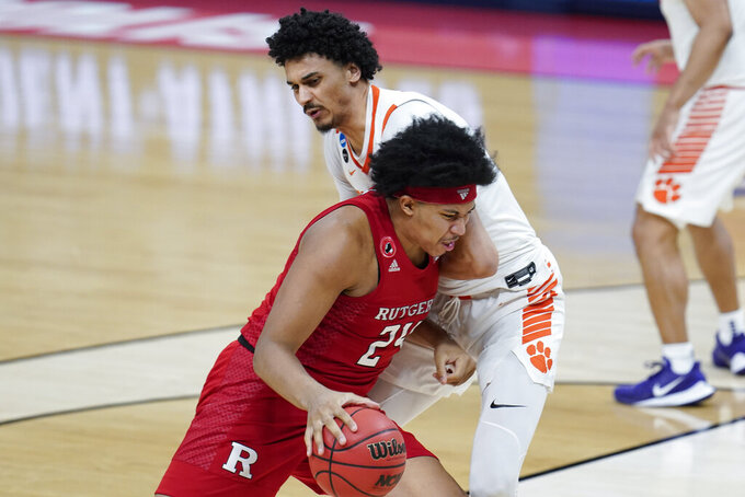 Rutgers guard Ron Harper Jr. (24) drives on Clemson guard Chase Hunter (3) during the second half of a men's college basketball game in the first round of the NCAA tournament at Bankers Life Fieldhouse in Indianapolis, Friday, March 19, 2021. (AP Photo/Paul Sancya)
