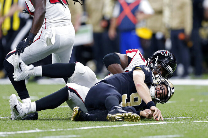 New Orleans Saints quarterback Drew Brees (9) grimaces after being brought to the ground by Atlanta Falcons defensive tackle Grady Jarrett in the first half of an NFL football game in New Orleans, Sunday, Nov. 10, 2019. (AP Photo/Rusty Costanza)