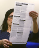An elections worker examines a ballot before inserting it into a counting machine at Pima County Elections in Tucson, Ariz., Monday, Nov. 12, 2018.  (Rick Wiley/Arizona Daily Star via AP)
