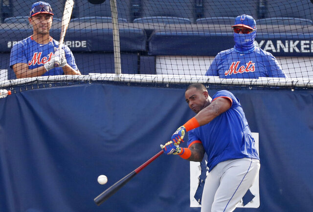 New York Mets Michael Conforto, left, watches as Yoenis Cespedes takes batting practice in the cage before an exhibition game against the New York Yankees, Sunday, July 19, 2020, at Yankee Stadium in New York. (AP Photo/Kathy Willens)