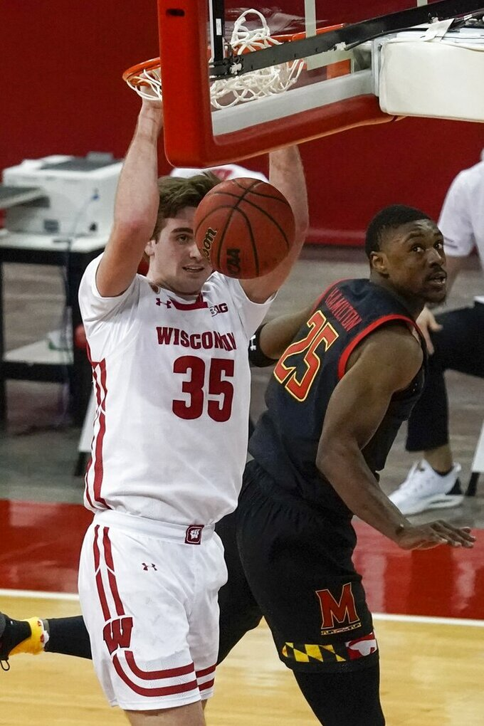 Maryland's Jairus Hamilton watches as Wisconsin's Nate Reuvers dunks during the second half of an NCAA college basketball game Monday, Dec. 28, 2020, in Madison, Wis. (AP Photo/Morry Gash)