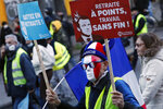 A protester holds a banner with French President Emmanuel Macron reading