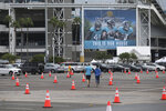 FILE - In this Sept. 13, 2020 file photo, fans walk through a parking lot with cones to social distance the cars before an NFL football game between the Jacksonville Jaguars and the Indianapolis Colts in Jacksonville, Fla.  The Jacksonville Jaguars are the latest NFL team dealing with a positive COVID-19 test. The Jaguars released a statement Saturday, Oct. 17,  saying a practice squad player was confirmed as testing positive for the coronavirus a day earlier.  (AP Photo/Stephen B. Morton, File)