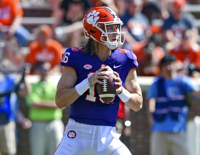 FILE - In this April 6, 2019, file photo, Clemson's Trevor Lawrence drops back to pass during Clemson's annual Orange and White NCAA college football spring scrimmage in Clemson, S.C. Clemson's defense was a big reason why the Tigers won a second national championship in three seasons. Now that unit has massive holes to fill after losing its entire front to the NFL, along with three key linebackers and two members of the secondary _ and that could mean the Tigers have to win shootouts behind quarterback Trevor Lawrence to stay on top. (AP Photo/Richard Shiro, File)