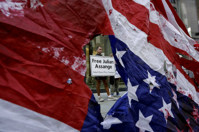 A supporter of WikiLeaks founder Julian Assange is seen through a hole torn in a defaced U.S. flag during a protest outside the Central Criminal Court, the Old Bailey, in London, Monday, Sept. 14, 2020. The London court hearing on Assange's extradition from Britain to the United States resumed Monday after a COVID-19 test on one of the participating lawyers came back negative, WikiLeaks said Friday. (AP Photo/Matt Dunham)