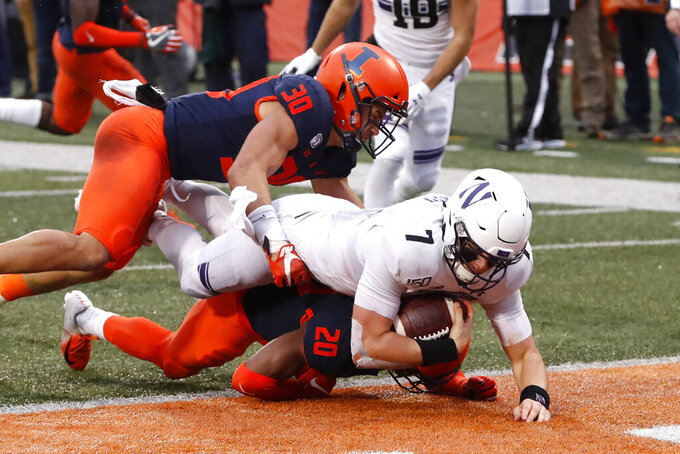 Northwestern quarterback Andrew Marty (7) dives over Illinois defensive back Nick Walker (20) and past Sydney Brown (30) for a touchdown during the first half of an NCAA college football game Saturday, Nov. 30, 2019, in Champaign , Ill. (AP Photo/Charles Rex Arbogast)