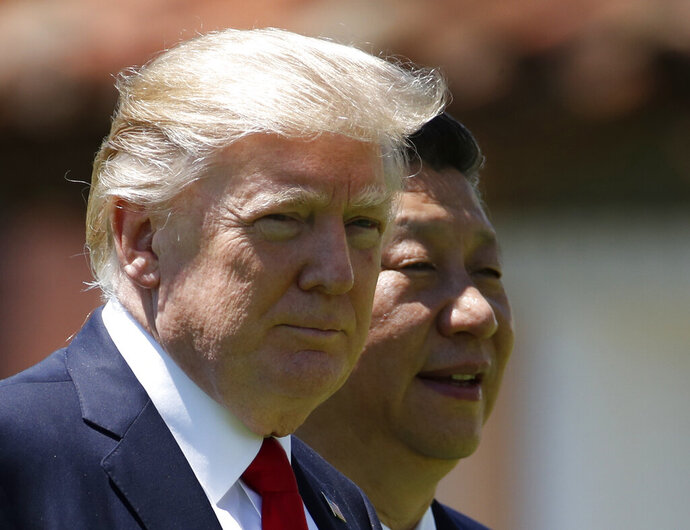 FILE - In this April 7, 2017, file photo, U.S. President Donald Trump, left, and Chinese President Xi Jinping walk together at Mar-a-Lago in Palm Beach, Fla. Foreign leaders showered President Donald Trump and his family with more than $140,000 in gifts during their first year in the White House, with China and Saudi Arabia among the most lavish givers. China's president gave Trump and his wife the two most expensive gifts in 2017: a $14,400 calligraphy display and a $16,250 dinnerware set featuring Trump's Mar-a-Lago resort. All gifts were turned over to the National Archives. (AP Photo/AlexBrandon, File)