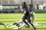 Hawaii running back Calvin Turner Jr. (7) is tackled by Portland State safety Xavier Bell (2) during the first half of an NCAA college football game, Saturday, Sept. 4, 2021, in Honolulu. (AP Photo/Darryl Oumi)